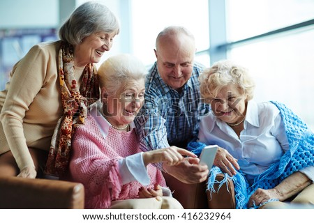 Group of senior friends watching photos on mobile phone