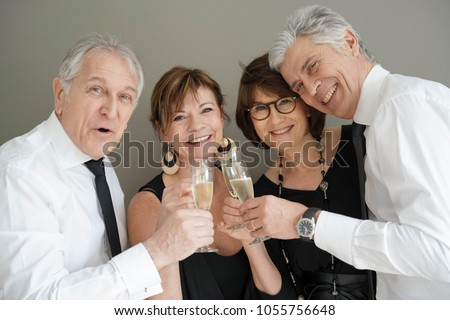 Group of senior people cheering with champagne