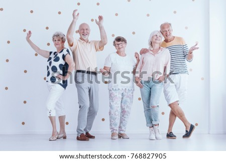 Group of senior people dancing together during a birthday party in bright room with gold dots wallpaper