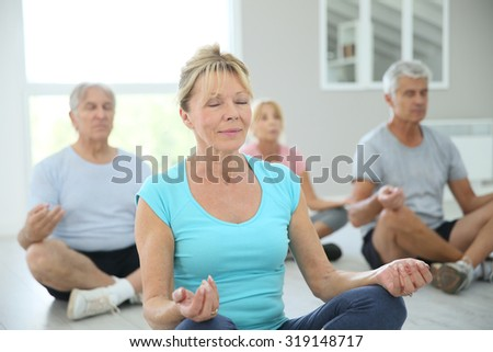 Group of senior people doing yoga exercises