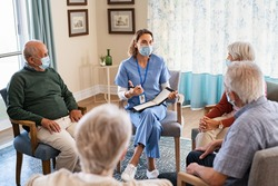 Group of senior people listening to nurse wearing face mask. Counselor wearing surgical mask talking to group of old people. Psychological support for elderly and lonely people in a community centre.