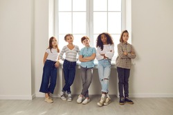 Group of serious diverse kids looking at camera standing by window with arms folded in hall at school or educational center. Success, confidence in future, conflict resolution in children's community