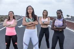 Group of serious diverse ladies with crossed arms standing on road and looking at camera during running training in outskirts