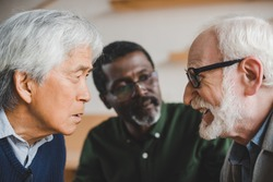 group of serious multiethnic senior friends playing staring contest
