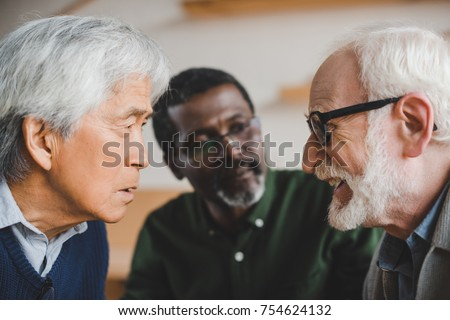 group of serious multiethnic senior friends playing staring contest - Shutterstock ID 754624132