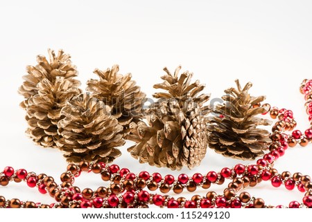 Group of seven golden pines cones and red garland on white background