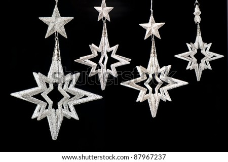 group of shiny silver stars on black background. christmas decoration. selective focus