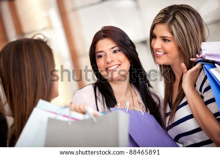 Group of shopping women talking at a store and holding with bags - stock photo