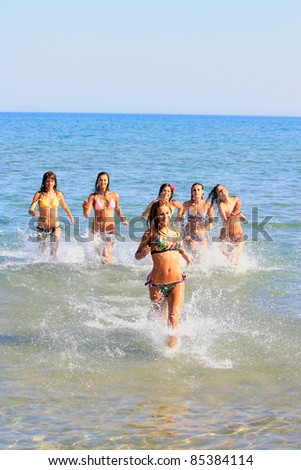 Group of Six Attractive girls splashing water in the sea in Greece