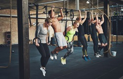 Group of six attractive young male and female adults doing pull ups on bar in cross fit training gym with brick walls and black mats