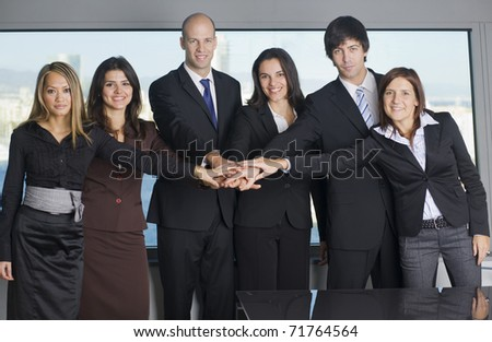Group of six businesspeople putting their hands on one hand