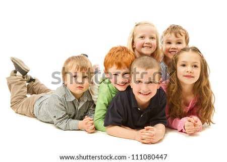 Group of six children laying down on other kids on floor together. Isolated on white. - stock photo