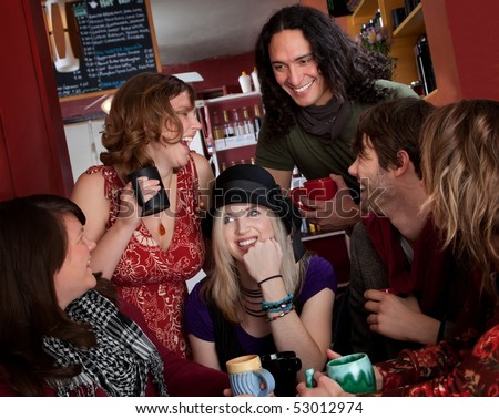 Group of six friends laughing over coffee