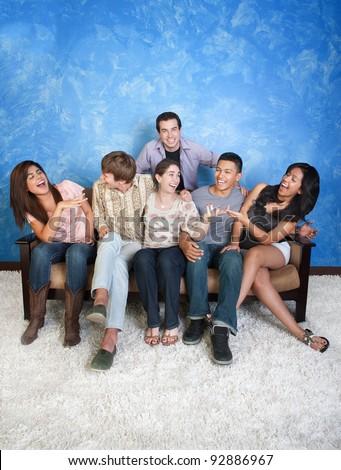 Group of six happy friends on sofa having fun