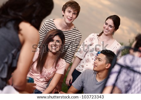 Group of six happy young people outside