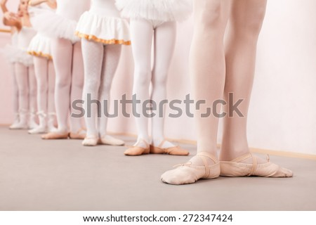Group of six little ballerinas standing in row behind their ballet teacher and practicing ballet. They are all good friend and amazing dance performers