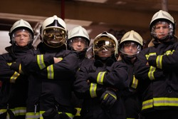 Group of six professional firefighters standing together. Firefighters wearing uniforms and protective helmets.