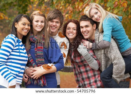 Group Of Six Teenage Friends Having Fun In Autumn Park