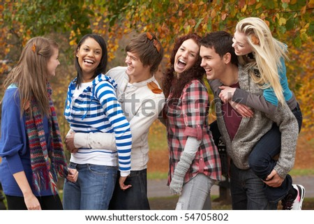 Group Of Six Teenage Friends Having Fun In Autumn Park