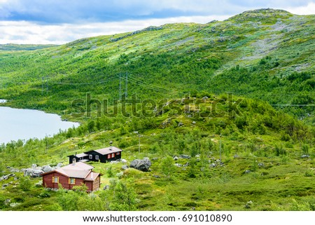 Group of small lakeside cabins in mountainous landscape. Powerlines on the mountainside. Mountain peak in background. Location Hardangervidda in Norway. #691010890