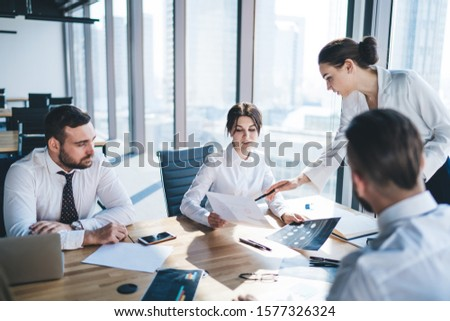 Group of smart business coworkers discussing documents and working process checking and analyzing information sitting at table in light office