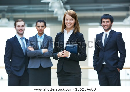 Group of smart businesspeople with happy female leader in front