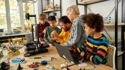 Group of smart kids listening to their male teacher while looking at 3d printer and plastic detail prototype at robotics school lesson. Science and education. Inventions and creativity for kids
