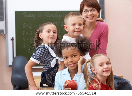 Group of smart schoolkids and their teacher looking at camera in classroom