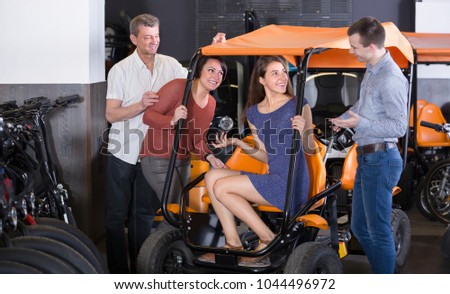 Group of smiling adult friends hiring grand tour electric at rental store. Selective focus