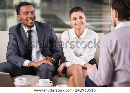Group of smiling business partners are interacting in office during coffee break.