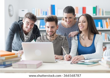 Group of smiling college students using a laptop and studying together in the classroom, education and friendship concept