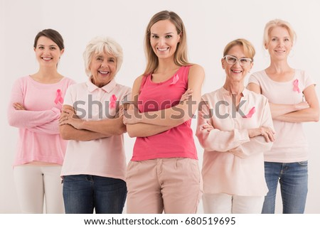 Group of smiling confident women wearing pink