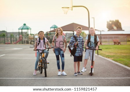 Group of smiling elementary school students on their way home. Back to school concept photo. Diverse group of real kids