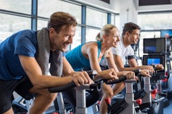 Group of smiling friends at gym exercising on stationary bike. Happy cheerful athletes training on exercise bike. Young men and woman working out at a class in the gym.