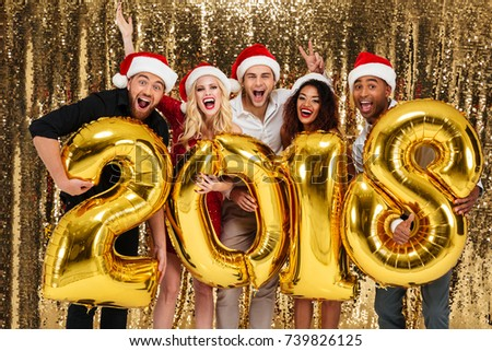 Group of smiling friends celebrating New Year while standing with golden balloon 2018 numbers and looking at camera isolated over shiny golden background
