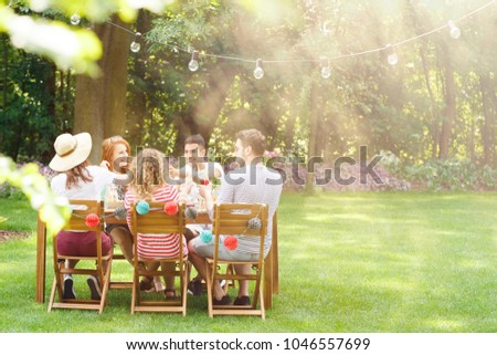 Group of smiling friends eating lunch at  a garden party
