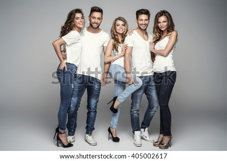 Group of smiling friends in fashionable jeans