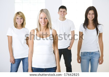 Group of smiling friends standing and looking at camera. They have on white t-shirt. Front view.