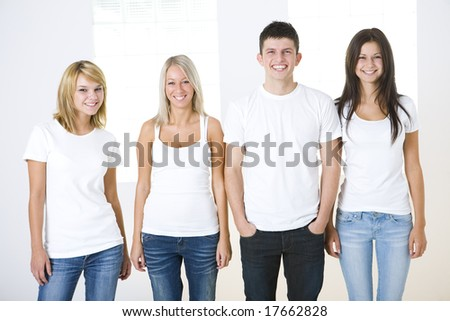 Group of smiling friends standing and looking at camera. Theyl have on white t-shirt. Front view.