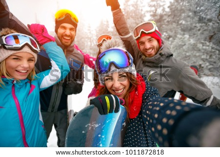 Group of smiling friends with ski on winter holidays - Skiers having fun on the snow and making selfie