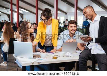 Group of smiling inspired young business people working together in office