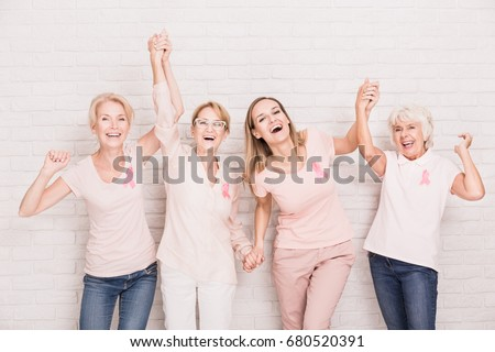 Group of smiling ladies with pink ribbons cheering and holding hands