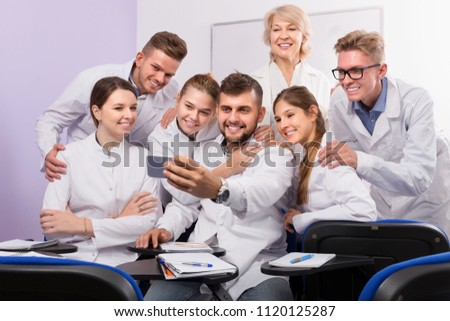 Group of smiling medical students and female professor taking selfie in auditorium #1120125287