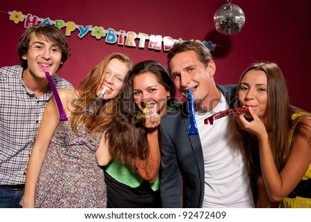 Group of smiling people with funny pipes at birthday party