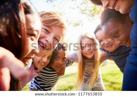 Group of smiling schoolchildren lean in to camera embracing Foto stock ©