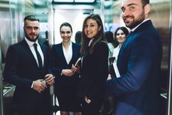 Group of smiling successful people in suits carrying documents while standing together and looking at camera in elevator cabin at urban office building