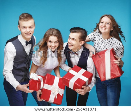 Group of smiling young people holding presents wrapped in red gift paper. Hipster style. Blue background. Standing together happy smile give wrapped giftboxes