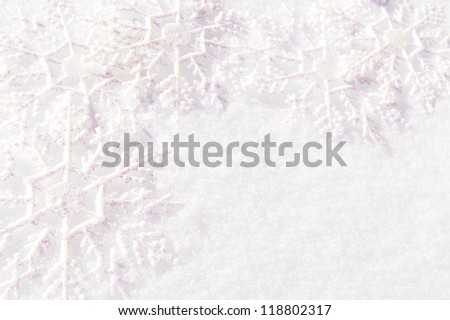 Group of snowflake decorations resting in fresh snow forming a border