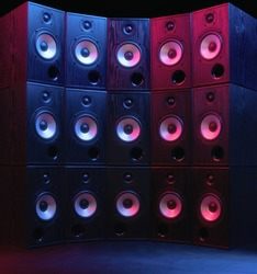 Group of sound speakers in neon light on black.