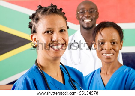 group of south african medical workers portrait in front of south african flag